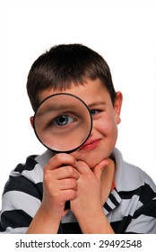 A young boy peers through a magnifying glass.