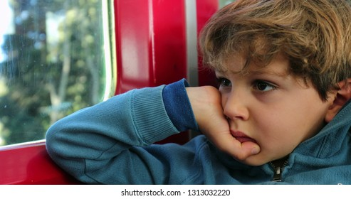 Young boy with a pensive look on his face starring at tram window. Child  with 59a50fb8c6aac