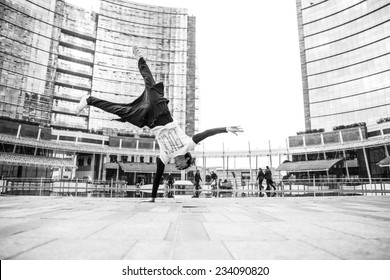 young boy performing parkour move in the center of Milan. concept about recreation and leisure