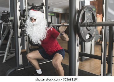 Young boy performs squats on legs training with Santa Claus costume ready to burn the calories of Christmas