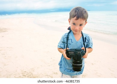 young boy with photo camera on beach background