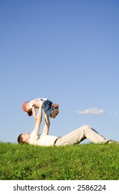 Young boy play with father. Green grass. Blue sky. 3