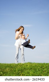 Young boy play with mother. Blue sky. Green grass. 5