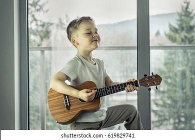 Young boy play on guitar at home at sunny day. Boy play on ukulele - hawaiian guitar.