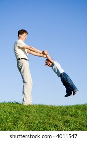 Young boy played with father. Green grass. Blue sky. 11