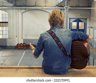 Young boy playing the acoustic guitar inside a hall; back view