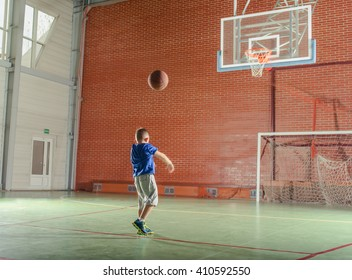 Young boy playing basketball on an indoor court tossing the ball at the goal as he practices his game