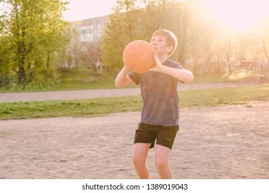 Young boy playing basketball taking aim with the ball at the goal with a look of concentration backlit with flare from the evening sun