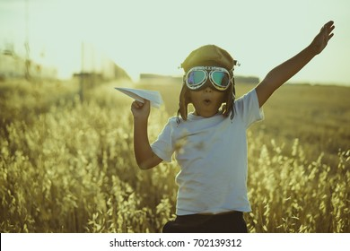 Young Boy playing to be airplane pilot, funny guy with aviator cap and glasses, carries in his hand a plane made of paper
