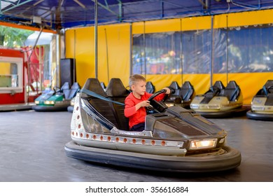 Young boy playing in a bumper car at an amusement park steering himself around the track with a look of concentration, side view