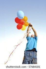 Young boy playing with a bunch of balloons outside