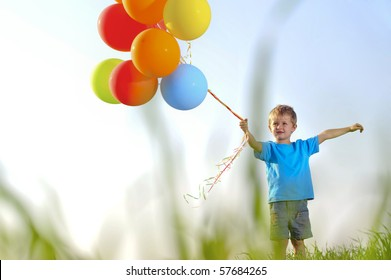 Young boy playing with a bunch of balloons outside, shot through grass in the field