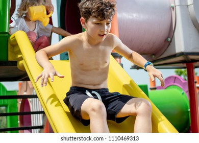 Young boy playing carefully on a plastic slide in a children playground park