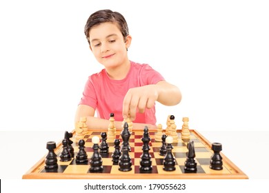Young boy playing chess seated at a table isolated on white background