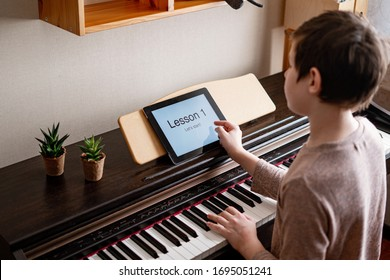 Young boy playing classic digital piano at home during online class at home, social distance during quarantine, self-isolation, online education concept