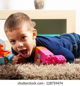 Young boy playing with cubes on the carpet