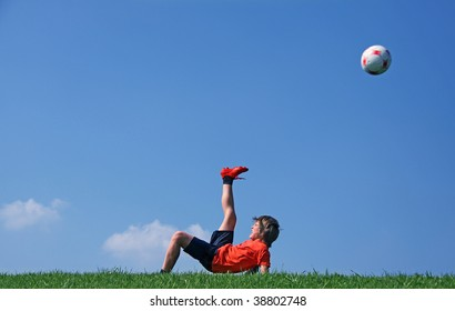 young boy playing with the football