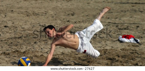 young boy playing football on the beach