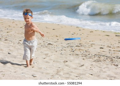 young boy playing frisbee on beach