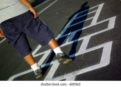 Young boy playing a game of hopscotch.