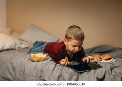 Junge Junge, der Spiele auf digitalen Tablets spielt und Jung Food isst.Online-Spiele süchtig
