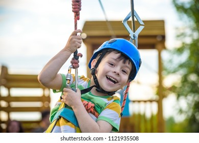 Young boy playing and having fun doing activities outdoors. Happiness and happy childhood concept. Boy swing on rope.