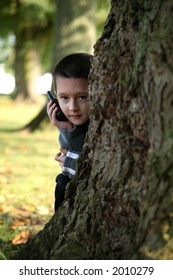 Young boy playing hide and seek holding a mobile phone