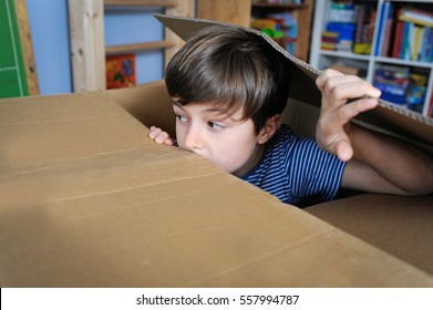 Young boy is playing hide and seek inside a cardboard box in his room
