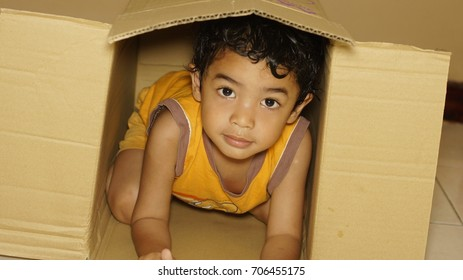 Young boy playing hide and seek in a box