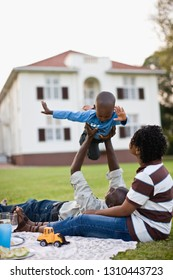 Young boy playing with his young adult father while picnicking with his mother.