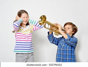 Young boy is playing his trumpet and is annoying his teenage sister with the noise