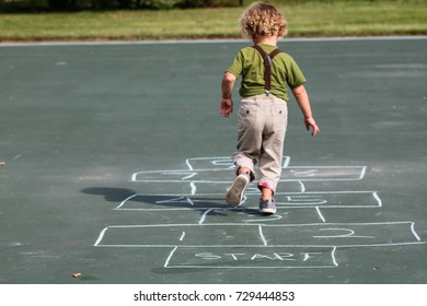 A young boy playing hop scotch at the playground