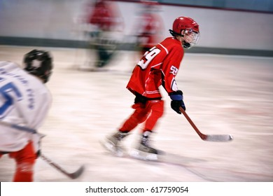 young boy playing ice hockey on the rink