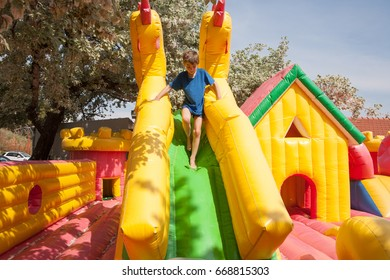 Young boy playing in an inflatable toy house in a park