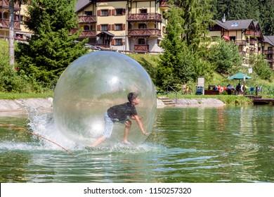 Young boy playing inside a floating water walking ball. Aquazorbing in Hrabovo, Ruzomberok