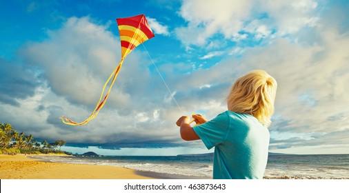 Junge Junge, der mit Drachen am Strand spielt