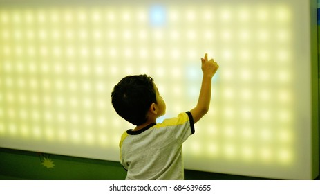 Young boy playing with led light interaction wall