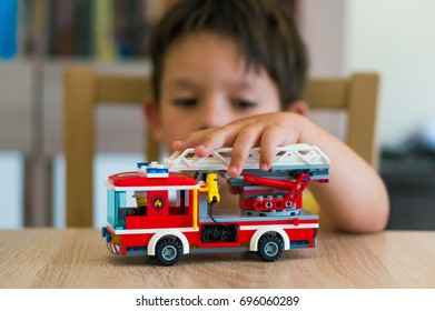 Young boy playing with Lego City fire truck on a wooden table on August 2017 in Poznan, Poland