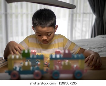 Young boy playing with Lego on a table in a room, Education Development