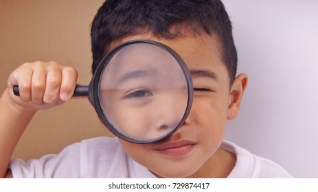 Young boy playing with magnifying glass isolated on white background