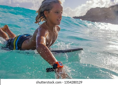 Young boy playing in the Ocean on his Boogie Board