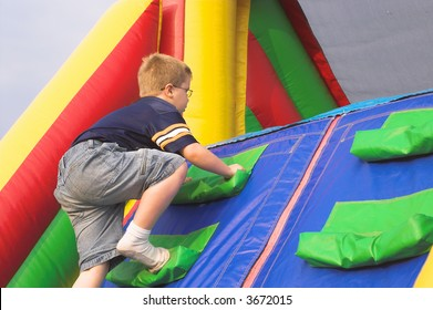 A young boy playing on a obstacle course.