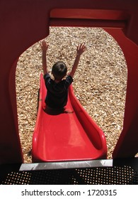 Young boy playing on slide with arms raised