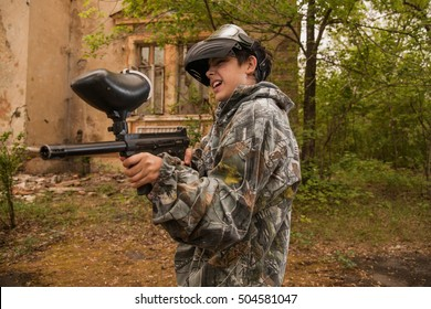 young boy playing paintball. boy aiming a paintball gun. Boy in camouflage clothing. boy in a protective suit. Boy in a protective mask. game of war. war game. Boy shoots a gun.