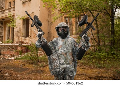 young boy playing paintball. boy aiming a paintball gun. Boy in camouflage clothing. boy in a protective suit. Boy in a protective mask. game of war. war game. boy holding two guns