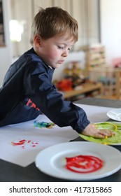 Young boy playing with paintings on his hands to develop his creativeness