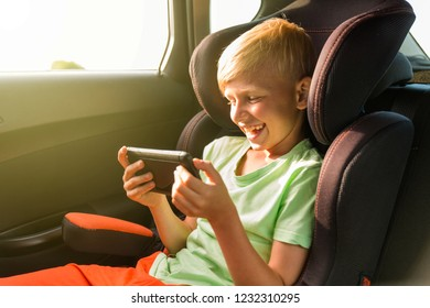 Young boy playing with phone in a car seat for children