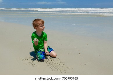 A young boy playing in the sand stops to look at the ocean