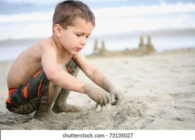 young boy playing in the sand and waves on the beach