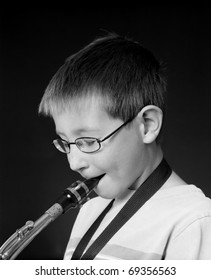 Young Boy playing a saxophone over black